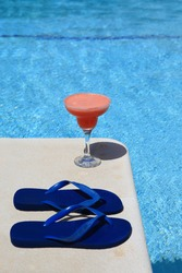 A decorated cocktail (strawberry Margarita) on the swimming pool border - Lifestyle concept