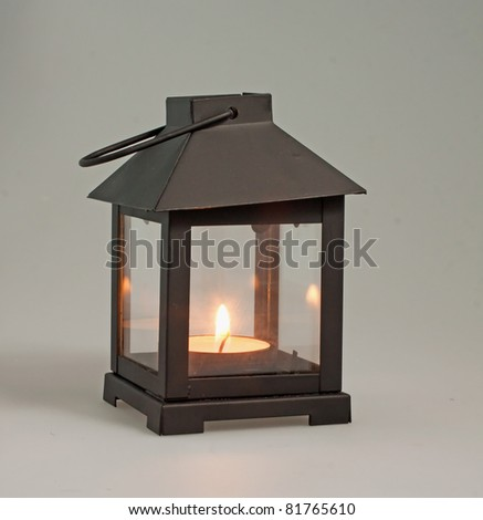 A decorative black lantern over a black mat with lit candle