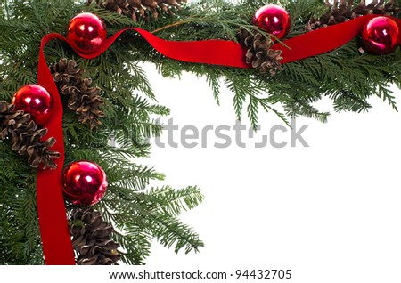 A decorative border of pine boughs ornaments cones and ribbon isolated on white
