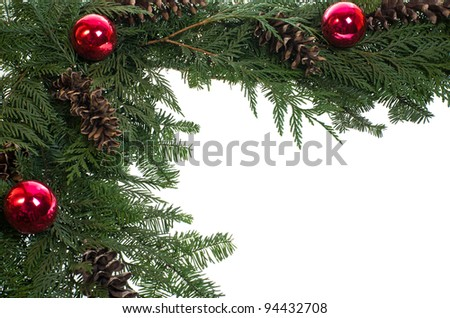 A decorative border of pine boughs ornaments cones isolated on white