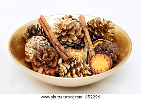 A decorative bowl with gold sprayed organic and natural items