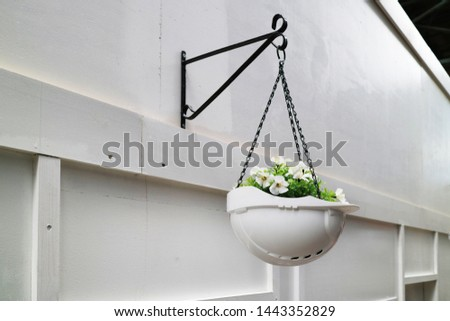 A decorative composition of a white construction helmet and flowers hangs on a metal bracket on a wooden construction fence in the city in honor of the builder's day