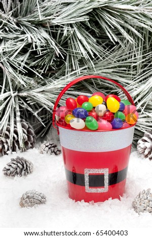 A decorative pail of Christmas candy in a snowy wilderness.  Open space for copy intentionally left in the upper image tree area.