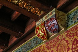 A decorative piece of English heraldry featuring two shields, on a traditionally decorated wall and ceiling area