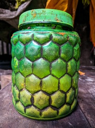 A decorative plastic green jar that is used as a spice container has become rusty and half discoloured.