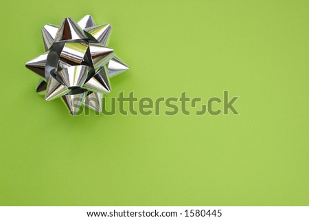 A decorative star, made from silver ribbon, on a plain green background with space for text (copy).