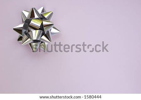 A decorative star, made from silver ribbon, on a plain lilac background with space for text (copy).