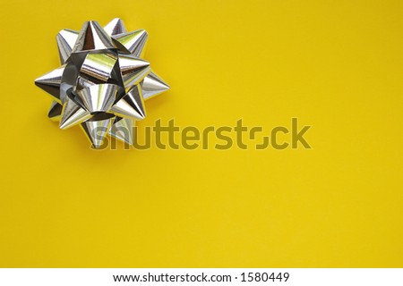 A decorative star, made from silver ribbon, on a plain yellow background with space for text (copy).