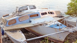 A decrepit damaged old wooden catamaran abandoned in a state of disrepair run ashore on a mangrove river bank