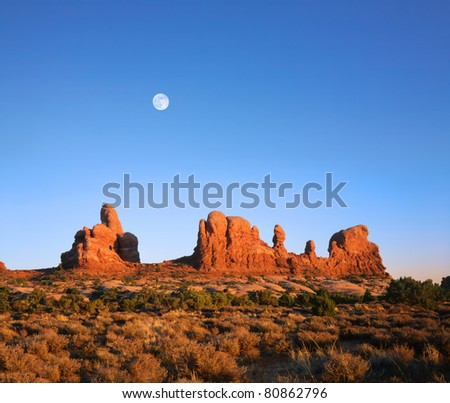 A Deep Blue Afternoon Sky And Daylight Full Moon Rising Over Red Sandstone Rock Forms At Arches National Park, Utah, USA