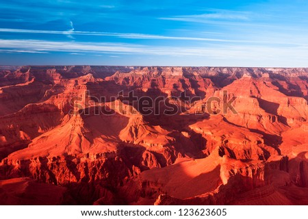 A deep orange sunset at the Grand Canyon turns the mountains a vibrant orange.