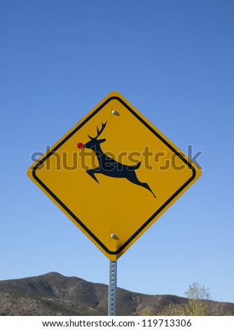 A deer crossing warning sign with a red sticker on the nose to make the deer look like Rudolph the red-nosed reindeer.