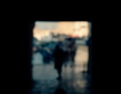 A defocused, blurred shot of a passageway from an old medieval town to the seaport, with some unrecognizable passersby.