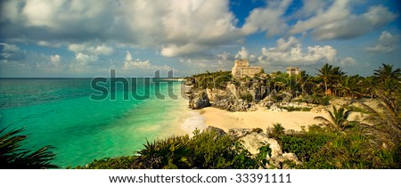 A 110-degree panoramic image of the main temple structure and Gulf of Mexico in the ancient Mayan city at Tulum, Mexico.