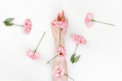 A delicate female hand, on top of which are flowers of pink eustoma. White background. Flat lay. The concept of Floristics and tenderness