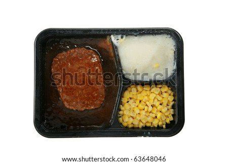 a delicious and nutricous  classic salisbury steak tv dinner with mashed potatoes and corn in its black plastic tray, isolated on white
