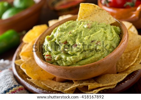 A delicious authentic mexican guacamole dip with avocado, lime, and tomato.