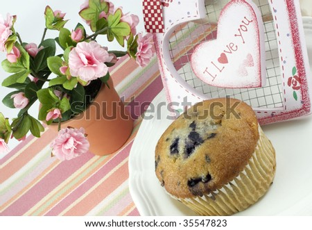 A delicious blueberry muffin on a plate with a pink feminine setup and a heart with I Love You written on it, diagonal viewpoint