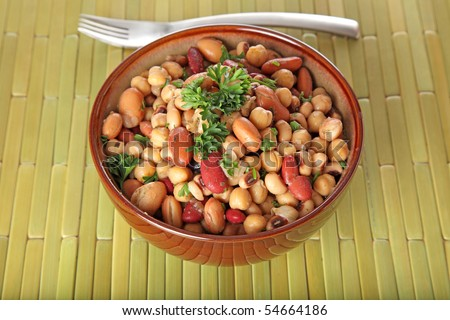 A delicious bowl of bean salad on a green bamboo placemat.