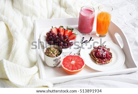 A delicious brakfast in bed with juice, smoothie, fruit, granola and pancakes