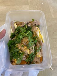 A delicious Cantonese style rice noodle roll served with beef, egg and coriander in a take away plastic lunch box. Photo taken in Hong Kong