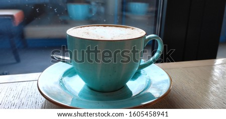 A delicious cappuccino is poured into a blue cup. The cup is on the saucer.