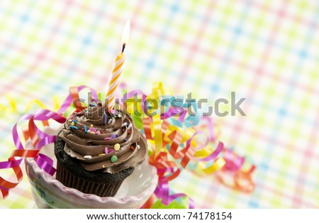 A delicious chocolate cupcake with one lit candle and colorful party ribbons
