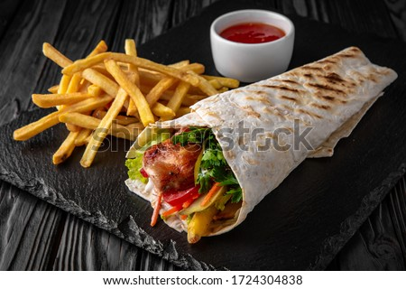 A delicious doner donair kebab wrap with meat, lettuce, tomato, red onion and sauce with french fries and sauce.