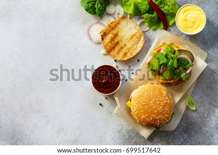 A delicious fresh homemade hamburger on a slate or stone table. Cheeseburger with meatball and vegetables. Street food, fast food. Top view with copy space.