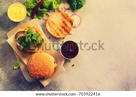 A delicious fresh homemade hamburger on a slate or stone table. Cheeseburger with meatball and vegetables. Street food, fast food. Top view with copy space. Toned image. #703922416
