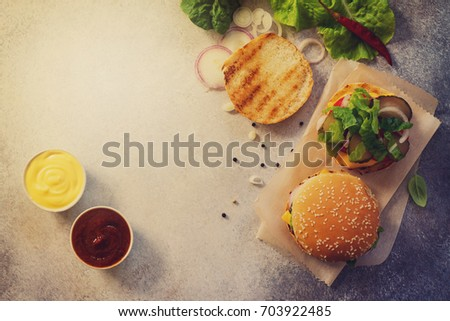 A delicious fresh homemade hamburger on a slate or stone table. Street food, fast food. Top view with copy space. Toned image. #703922485