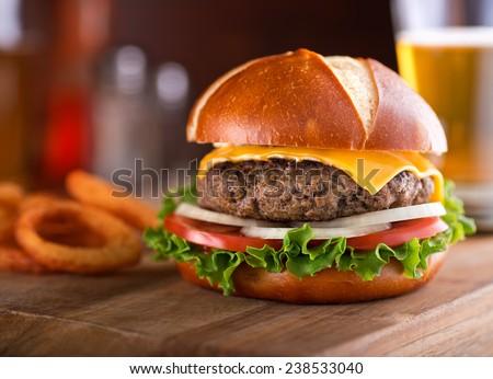 A delicious gourmet cheeseburger on a pretzel bun with lettuce, onion, and tomato.