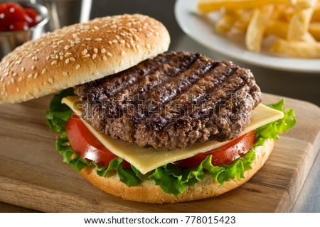 A delicious grilled Angus burger with cheese, lettuce, and tomato on a sesame seed bun.