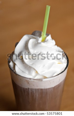A delicious iced coffee drink topped with fresh whipped cream.  Shallow depth of field.