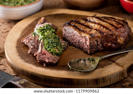 A delicious medium rare fire grilled argentina style steak with chimichurri verde sauce. #1179909862