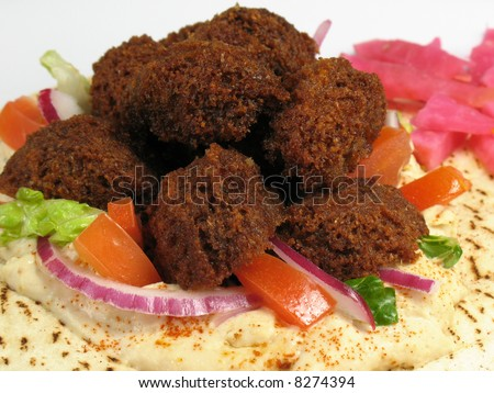 A delicious portion of falafels served on top of a pita bread with hummus, lettuce, tomato, red onions, and a side of turnips pickled in beet roots.