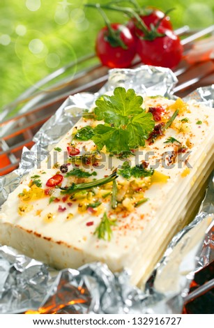 A delicious portion of feta cheese or halloumi topped with fresh herbs and spices grilling on an outdoor barbecue
