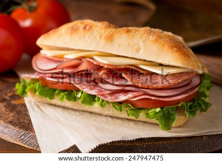 A delicious sandwich with cold cuts, lettuce, tomato, and cheese on fresh ciabatta bread.