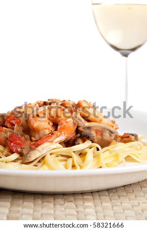 A delicious shrimp scampi over linguine dish along with a glass of pinot grigio white wine.