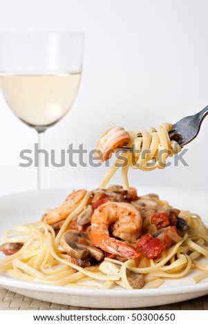 A delicious shrimp scampi pasta dish along with a glass of pinot grigio white wine.  Shallow depth of field with focus on the fork.
