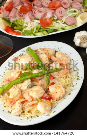 A delicious shrimp scampi pasta dish with antipasto salad in the background.