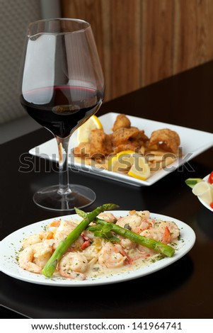 A delicious shrimp scampi pasta dish with red wine and friend shrimp appetizer in the background.