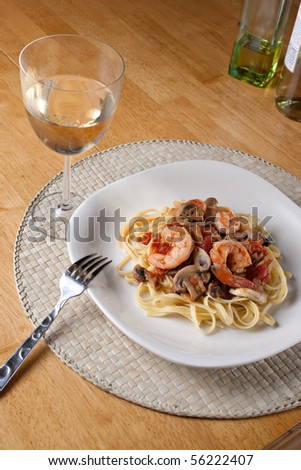 A delicious shrimp with linguine pasta dish and a nice glass of pinot grigio white wine.