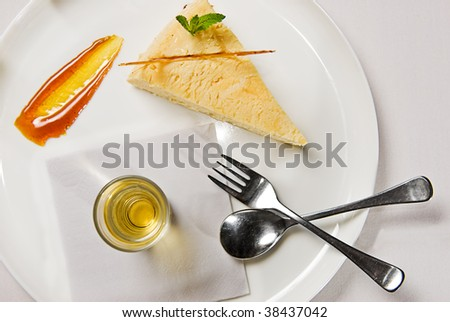 A delicious slice of cheesecake served with toffee, syrup and a dessert shot.
