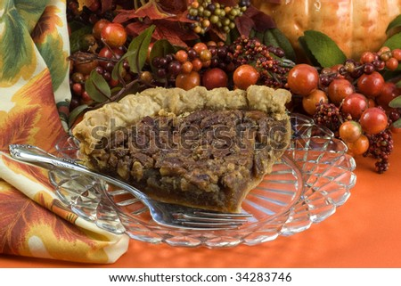 A delicious slice of homemade pecan pie on a crystal plate with fall decorations, horizontal with copy space