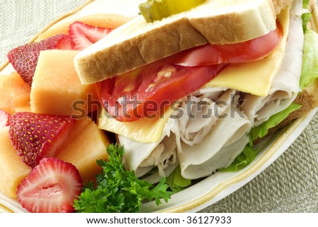 A delicious turkey sandwich filled with sliced turkey, tomatoes, cheese and lettace on toasted bread with fresh strawberries and cantaloupe, diagonal viewpoint, closeup