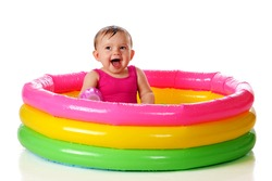 A delighted baby girl in a colorful kiddie pool.  Isolated on white.