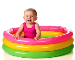 A delighted baby girl playing in a water-filled kiddie pool.  Isolated on white.