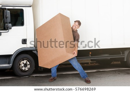 A Delivery Man Or Mover Holding Heavy Box In Front Of The Van