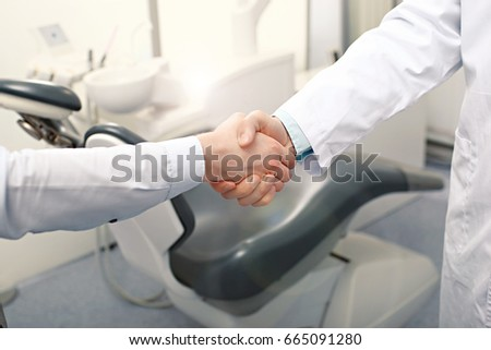A dentist and a patient are handshaking. Invitation to the dental clinic concept